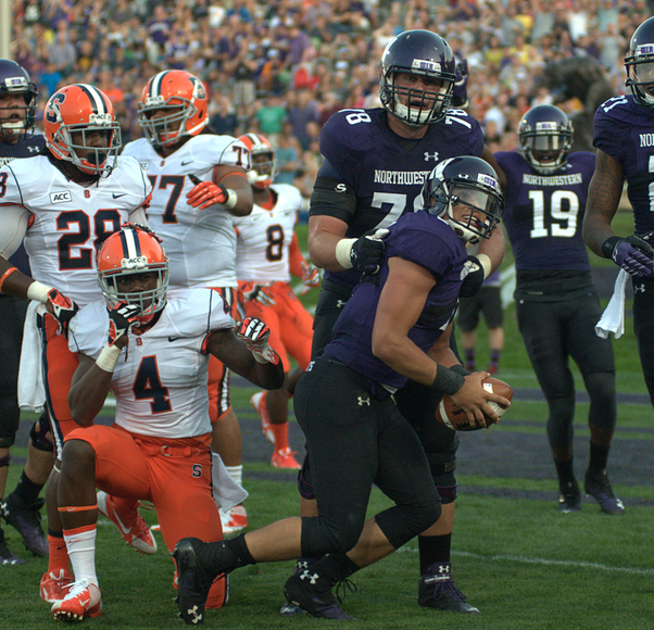 Northwestern quarterback Kain Colter celebrates as cornerback Brandon Reddish (4) and the rest of the Syracuse defense look on. Colter rushed for 102 yards to go along with 116 through the air.